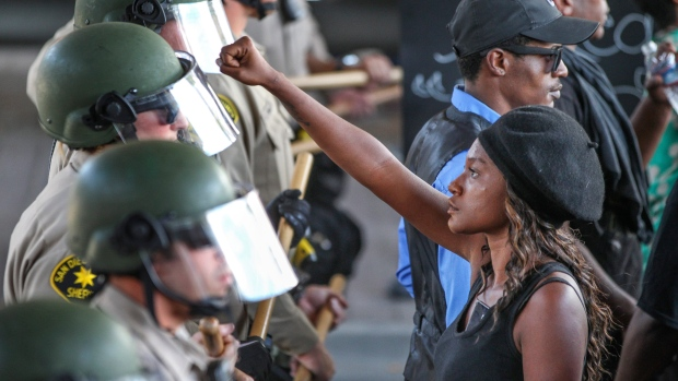 Ebonay Lee holds up her fist toward a line of Sheriff's deputies as she and other people protest Wednesday, Sept. 28, 2016, in El Cajon, Calif. (Hayne Palmour IV / San Diego Union-Tribune via AP)