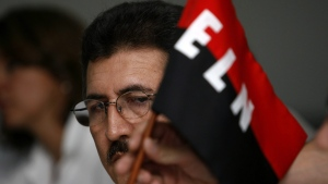 In this Oct. 29, 2006, file photo, Antonio Garcia, leader of the National Liberation Army (ELN), looks at his rebel group's flag during a press conference at the Palco hotel in Havana. (AP photo/ Javier Galeano, File)