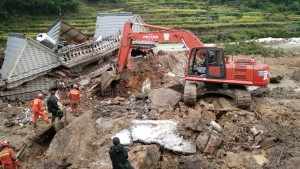 Rescuers use heavy equipment to dig in the rubble of a house that was destroyed in a landslide in Sucun village in eastern China's Zhejiang Province Thursday, Sept. 29, 2016. (Chinatopix via AP)