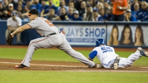 Toronto Blue Jays' Russell Martin is out as he slides into first base as Baltimore Orioles' Chris Davis, left, makes the catch during the first inning of MLB baseball action in Toronto on Thursday, Sept. 29, 2016. (Mark Blinch / THE CANADIAN PRESS)