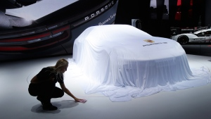 A worker adjusts the sheet around a car at the Porsche stand during the Paris Motor Show in Paris, France on Sept. 29, 2016. (Michel Euler / AP)