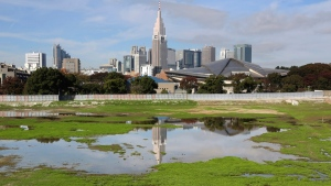 A skyscraper reflects in A pool of water in the site of Japan's National Stadium demolished for the renovation for the 2020 Olympic games in Tokyo, seen on Nov. 16, 2015.(Koji Sasahara / AP)