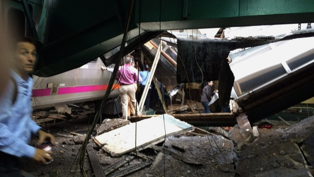 People examine the wreckage of a New Jersey Transit commuter train that crashed in Hoboken,, N.J., on Sept. 29, 2016. (William Sun via AP)