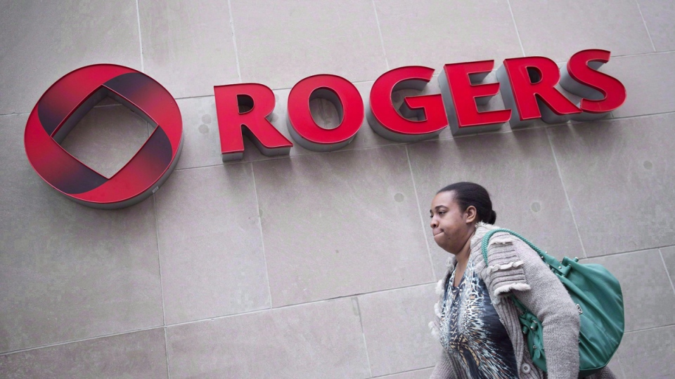 A pedestrian walks past the Rogers Building, in Toronto, on April 22, 2014. (THE CANADIAN PRESS / Darren Calabrese)