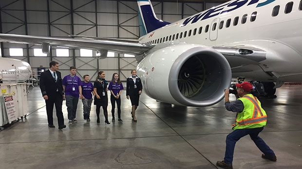 CTV Calgary videographer Keith MacDonald snaps a shot of the Calgary group in the WestJet hanger.