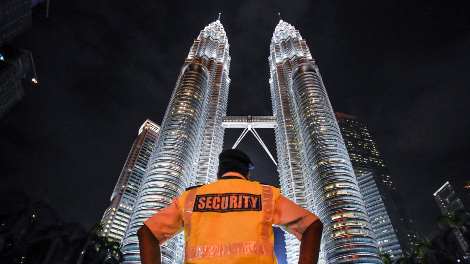 FILE - In this Jan. 14, 2016 file photo, a security guard stands guard in front of Malaysia's iconic building, Petronas Twin Towers in Kuala Lumpur, Malaysia. (AP Photo/Joshua Paul)