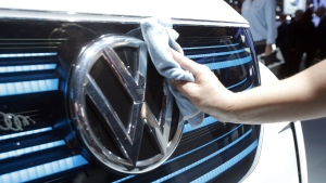 A worker shines the grill of a new Volkswagen electric car during a press conference at the Paris Motor Show in Paris, France, Thursday, Sept. 29, 2016. (AP / Michel Euler)