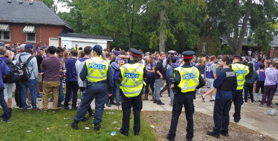London police keep their eye on the crowd gathered on Broughdale Avenue in London, Ont. on Saturday, October 1, 2016. (London Police / Twitter)