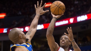 Toronto Raptors' DeMar DeRozan, right, shoots over Golden State Warriors' David West during second half pre-season NBA basketball action in Vancouver, B.C., on Saturday October 1, 2016. (THE CANADIAN PRESS / Darryl Dyck)