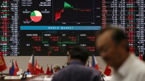Filipino traders walk in front of an electronic board showing world markets at the Philippine Stock Exchange on Oct. 16, 2014. (Aaron Favila / AP)