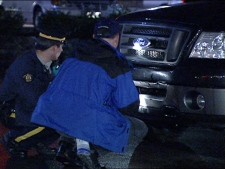 Police investigators in Langley, B.C. examine the front end of a pickup truck involved in a drive-by shooting on February 11, 2009.