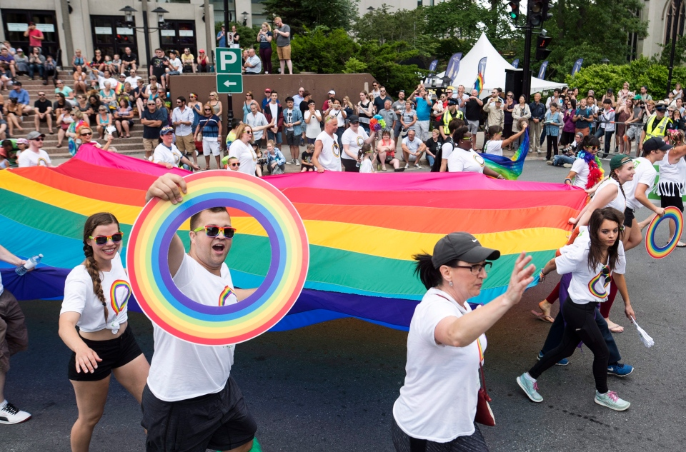 Revellers carry a large Pride flag while participating in the annual Halifax Pride parade in Halifax on Saturday, July 23, 2016. (THE CANADIAN PRESS / Darren Calabrese)