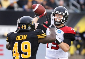 Calgary Stampeders quarterback Bo Levi Mitchell (19) passes as Hamilton Tiger Cats' Larry Dean defends during the first-half of CFL football action in Hamilton on Saturday, October 1, 2016. (THE CANADIAN PRESS/Peter Power)