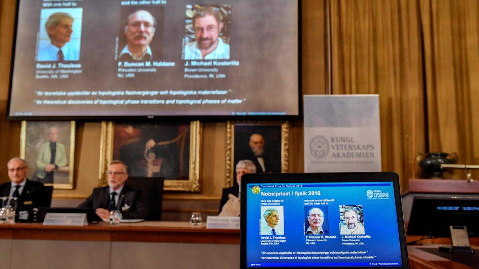 Royal Academy of Sciences members, from left, Professor Nils Martensson, Professor Goran K Hansson and Professor Thomas Hans Hansson reveal the winners of the Nobel Prize in physics, at the Royal Swedish Academy of Sciences, in Stockholm, Sweden, on Oct. 4, 2016. (Anders Wiklund /TT via AP)