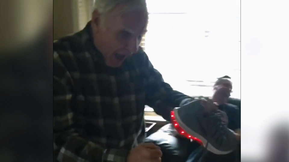 Ted Thorne, 70, reacts to a pair of Nike shoes with light-up heels in this still image from video posted on Instagram by his daughter, Sarah.