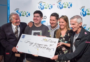 Patrick Lamothe and his wife Johanne Leblond, their son Yannick, centre, and Johanne's father Guy Leblond, right, all from Montreal, are presented with their cheque for the $37.5 million jackpot win in the September 30 Lotto Max draw by Guy Corbeil Tuesday, October 4, 2016 in Montreal. (THE CANADIAN PRESS/Paul Chiasson)