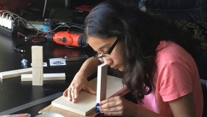 In this undated photo supplied by Ravi Naiknaware, Anushka Naiknaware works at her home in Beaverton, Ore, developing and testing a bandage that can tell medical workers when it's time for the dressing to be changed. (Ravi Kaiknaware via AP)