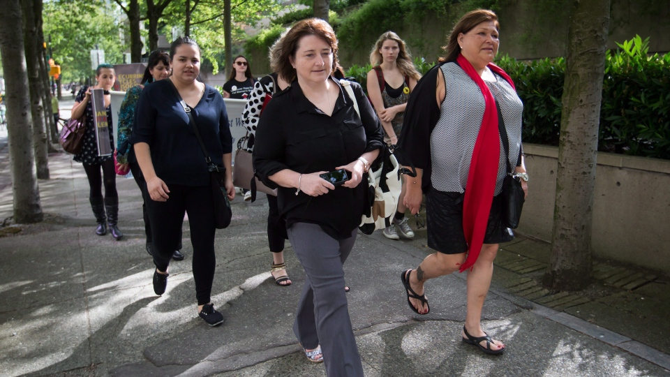 Former RCMP constables Janet Merlo, centre, of Nanaimo, B.C., and Marge Hudson, right, of Winnipeg, Man., arrive at B.C. Supreme Court for a hearing to seek certification of a class action lawsuit against the RCMP over sexual harassment and gender discrimination, in Vancouver, B.C., on Monday June 1, 2015. (THE CANADIAN PRESS / Darryl Dyck)
