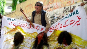 "Pakistani activists perform a skit in a street in Hyderabad, Pakistan, Thursday, Sept. 4, 2008, to portray the recent ""honor killings"" in a tribal town in Pakistan's Balochistan province with banner which reads ""Stop burying women in the name of honour killing."" (Pervez Masih/AP)"