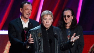 Alex Lifeson, centre, Neil Peart, left, and Geddy Lee, right, of Rush accept their band's induction into the Rock and Roll Hall of Fame on April 18, 2013 in Los Angeles. (Danny Moloshok / Invision / AP / THE CANADIAN PRESS)