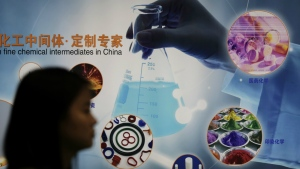 A woman walks past a display at the China International Chemical Industry Fair in Shanghai, China, on Thursday, Sept. 22, 2016. (AP / Andy Wong)