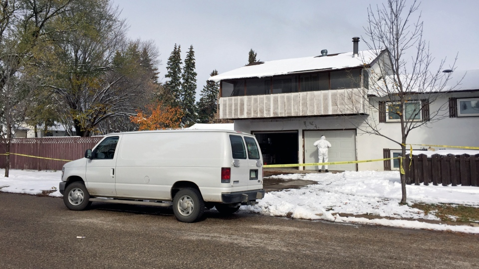 An officer investigates at an Avenue Q home in Saskatoon, one day after a Thursday, Oct. 6, 2016 incident that began with a break-and-enter call and ended hours later with a man dead inside the house. (Taylor Rattray/CTV Saskatoon)
