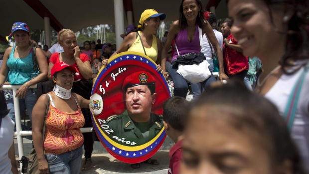 Government supporters hold an image of Venezuela's late President Hugo Chavez during a parade marking Venezuela's Independence Day in Caracas, Venezuela, Tuesday, July 5, 2016. Venezuela is marking 205 years of independence. (AP / Ariana Cubillos)