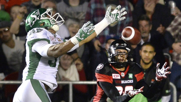 Ottawa Redblacks' Chris Williams (80) catches the ball to score a touchdown as he is defended by Saskatchewan Roughriders' Justin Cox (31) during first half CFL action on Friday, Oct. 7, 2016 in Ottawa. THE CANADIAN PRESS/Justin Tang