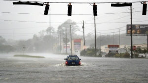 A motorist drives through a flooded street from Hurricane Matthew in Brunswick, Ga., Friday, Oct. 7, 2016. (AP Photo/David Goldman)