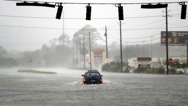 A motorist drives through a flooded street from Hurricane Matthew in Brunswick, Ga., Friday, Oct. 7, 2016. (AP Photo/David Goldman)