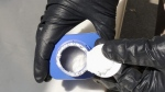 In this June 27, 2016 photo provided by the Royal Canadian Mounted Police, a member of the RCMP opens a printer ink bottle containing the opioid carfentanil imported from China, in Vancouver.