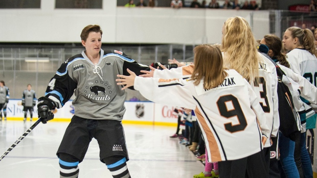 In this photo provided by the NWHL, date not known, Buffalo Beauts forward Harrison Browne high-fives fans during player introductions before a game in Buffalo, N.Y.