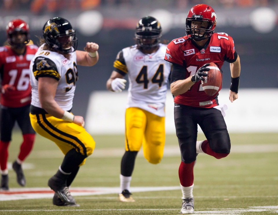 Calgary Stampeders quarterback Bo Levi Mitchell runs for a first down as Hamilton Tiger-Cats defensive tackle Linden Gaydosh and linebacker Taylor Reed look on during the third quarter of the 102nd Grey Cup in Vancouver, B.C. Sunday, Nov. 30, 2014. THE CANADIAN PRESS/Nathan Denette