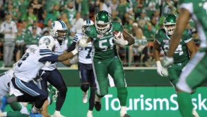 Saskatchewan Roughriders tackle Xavier Fulton muscles through a crowd during CFL action against the Toronto Argonauts, in Regina on Thursday, June 30, 2016. (Mark Taylor/The Canadian Press)
