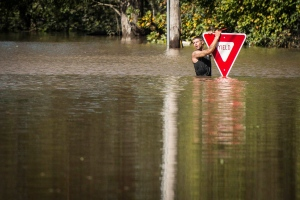 A man holds onto a yield sign after trying to swim out to help a truck driver who was stranded in floodwater from Hurricane Matthew, at U.S. Highway 301 and Tom Starling Road in Hope Mills, N.C., Sunday, Oct. 9, 2016. Both people were rescued. (Andrew Craft/The Fayetteville Observer via AP)