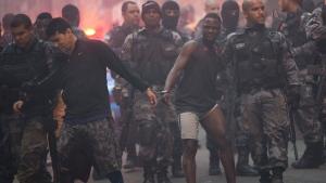 Police move a couple of handcuffed, recently detained men at Pavao Pavaozinho slum during a police operation in Rio de Janeiro, Brazil, Monday, Oct. 10, 2016. (AP Photo/Silvia Izquierdo)