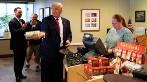 Republican presidential candidate Donald Trump holds up cookies during a visit to Eat'n Park restaurant, Monday, Oct. 10, 2016, in Moon Township, Pa. (AP Photo/ Evan Vucci)