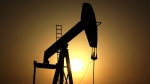 The sun sets behind an oil pump in the desert oil fields of Sakhir, Bahrain, on June 8, 2011. (Hasan Jamali / AP)