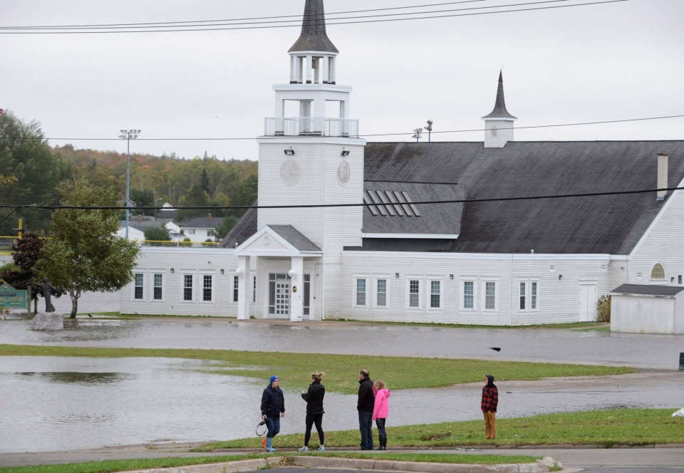 People look at the flooded area by St. Marguerite Bourgeoys Church in Sydney, N.S., Tuesday, Oct.11, 2016. (THE CANADIAN PRESS/Vaughan Merchant)
