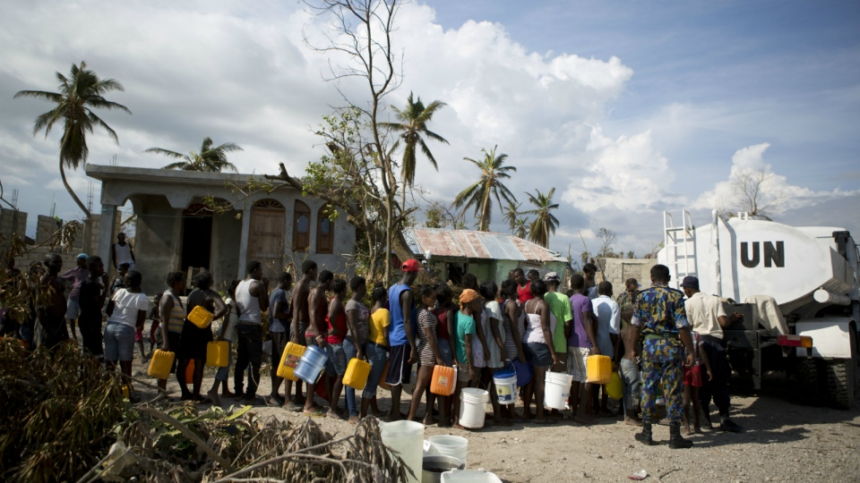 United Nations police from Bangladesh deliver drinking water to residents of Sous-Roche village, outside Les Cayes, Haiti on Tuesday, Oct. 11, 2016. (AP / Rebecca Blackwell)