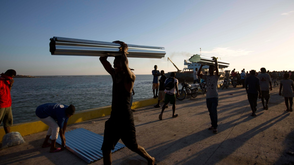 People carry metal sheets away from an aid ship that arrived after Hurricane Matthew hit Jeremie, Haiti, on Oct. 12, 2016. (Dieu Nalio Chery / AP)