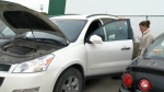 Mechanic Allister Henderson and Lea Williams-Doherty inspect the Vasquez family's 2010 Chevrolet Traverse