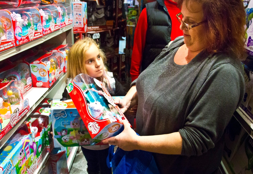 In this Friday, Nov. 27, 2015, file photo, Cinnamon Boffa, right, from Bensalem, Pa., checks out a 'Chubby Puppies' toy for her daughter Serenity, left, at a Toys R Us, in New York. (AP / Bebeto Matthews)
