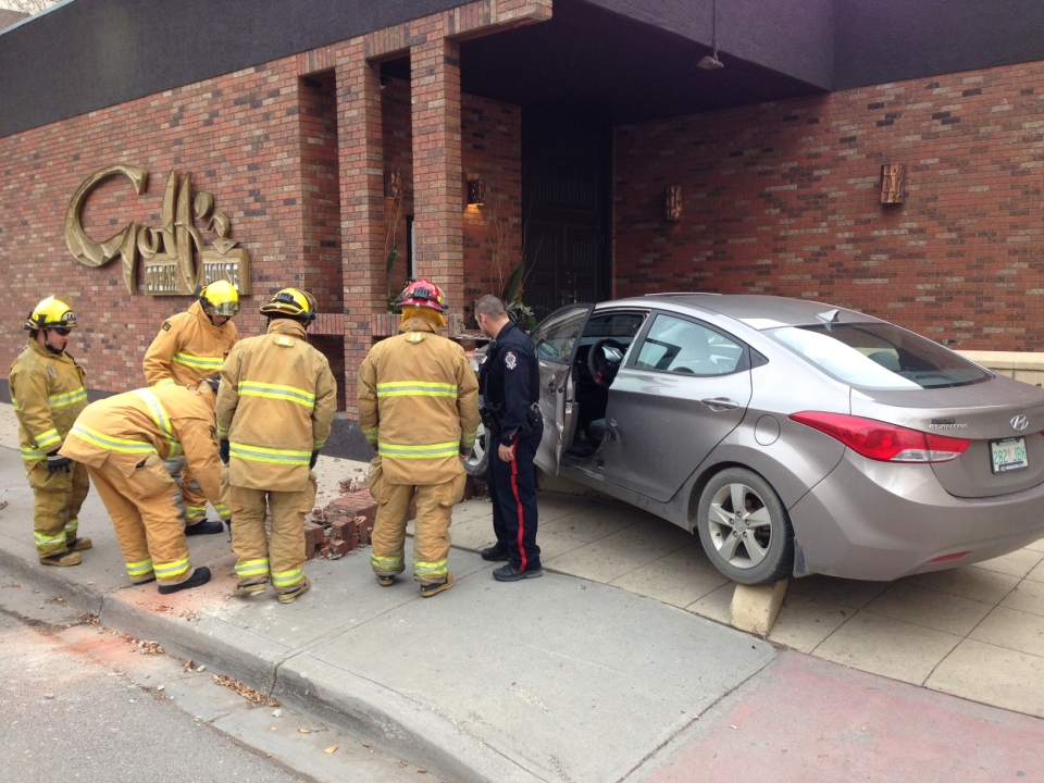 Police and emergency crews attend to the scene of a crash in which a car slammed into the side of Golf's Steak House in downtown Regina on Thursday, Oct. 13, 2016. (GARETH DILLISTONE/CTV REGINA)