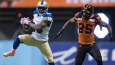 Winnipeg Blue Bombers' Kevin Fogg, left, intercepts a pass intended for B.C. Lions' Shawn Gore during the second half of a CFL football game in Vancouver, B.C., on Friday October 14, 2016. (Darryl Dyck/The Canadian Press)