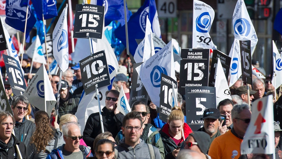 People march in Montreal, Saturday, October 15, 2016, to demand a $15 minimum hourly working wage in the province of Quebec and across Canada. (Graham Hughes / THE CANADIAN PRESS)