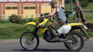 Donetsk People's Republic platoon commander Arsen Pavlov, also known as Motorola, rides a bike at a checkpoint outside Slovyansk, eastern Ukraine, on May 18, 2014. (Alexander Zemlianichenko / AP)