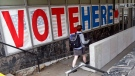 A voter passes a large sign before voting in Minneapolis, on Sept. 23, 2016. (Jim Mone / AP)