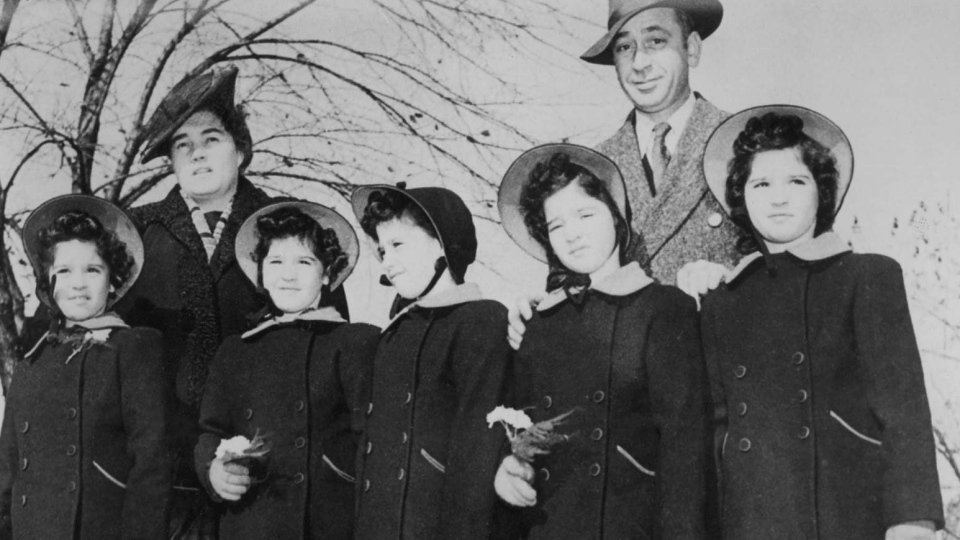 Elzire and Olivia Dionne stand with their quintuplets, Cecile, Yvonne, Marie, Emilie and Annette in this undated photo. (THE CANADIAN PRESS)