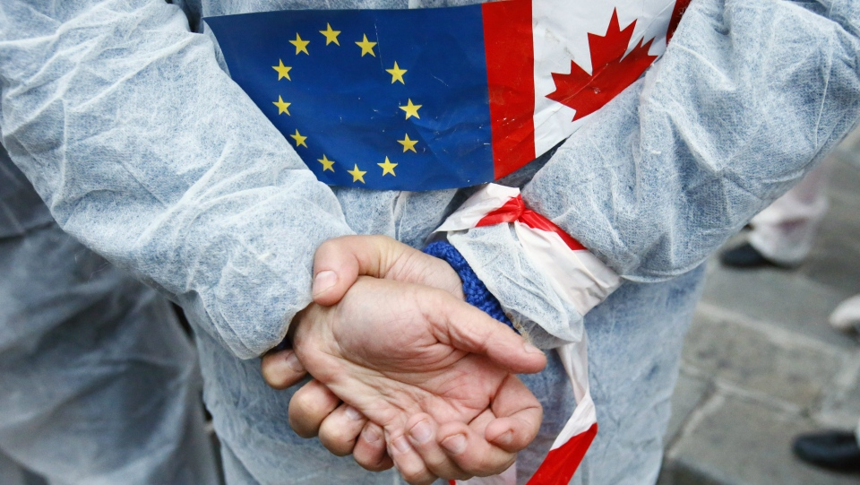 An activist demonstrates in front of French Agriculture ministry to protest against the EU trade deal with Canada, known as CETA, in Paris, Tuesday Oct. 11, 2016. (AP / Francois Mori)